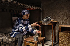 Angry female prisoner sitting on a bed and throws aluminum dishe Stock Images