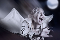 Angry female vampire with bangs. Attacking on night street royalty free stock photography