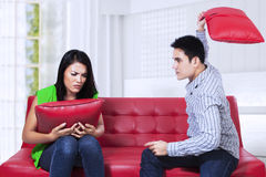 Angry fighting couple. Angry couple on red sofa fighting with pillow in the living room Royalty Free Stock Images