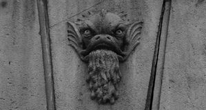 Angry fish bleeding by its mouth. Shot in black and white, detail on the sculpture on the facade of this historic building representing some characters / animals Stock Photos