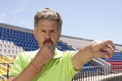 Angry football referee blowing a whistle Royalty Free Stock Image