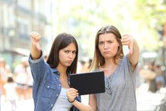 Angry friends holding a tablet with thumbs down. Two angry friends holding a tablet gesturing thumbs down in the street Stock Photos