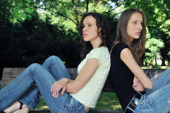Angry friends (teenage girls) in conflict. Friends outdoors series - two teenage girls are in conflick and do not speak with each another Royalty Free Stock Image