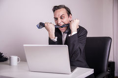 Angry and frustraded business man eating his tie in the office Royalty Free Stock Image