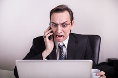 Angry and frustraded business man talking on a cell phone and screaming on his laptop in the office Royalty Free Stock Photo