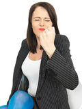 Angry Frustrated Business Woman. A DSLR royalty free image, of a young business woman, holding her fist up in anger having a temper tantrum. Against a white Stock Image
