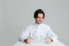 Angry frustrated man sitting at the table with water glass Stock Images