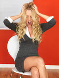 Angry Frustrated Woman Sitting in a Chair. A DSLR royalty free image, of attractive young secretary assistant, with long blonde hair, sitting on chair with legs Stock Photos