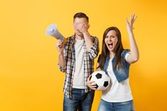Angry fun expessive couple, woman man football fans screaming, cheer up support team with soccer ball, megaphone. Isolated on yellow background. Sport family stock image