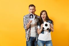 Angry fun expessive couple, woman man football fans screaming, cheer up support team with soccer ball, megaphone. Isolated on yellow background. Sport family stock photo
