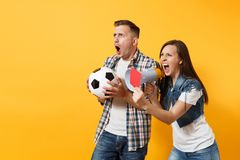 Angry fun expessive crazy couple, woman man football fans screaming, cheer up support team with soccer ball, megaphone. Red card isolated on yellow background royalty free stock photo