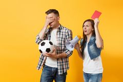 Angry fun expessive crazy couple, woman man football fans screaming, cheer up support team with soccer ball, megaphone. Red card isolated on yellow background stock image