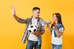 Angry fun expessive crazy couple, woman man football fans screaming, cheer up support team with soccer ball, megaphone. Red card isolated on yellow background stock photos