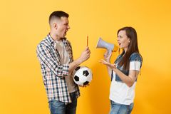 Angry fun expessive crazy couple, woman man football fans screaming, cheer up support team with soccer ball, megaphone. Red card isolated on yellow background stock photo