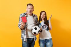 Angry fun expessive crazy couple, woman man football fans screaming, cheer up support team with soccer ball, megaphone. Red card isolated on yellow background royalty free stock image