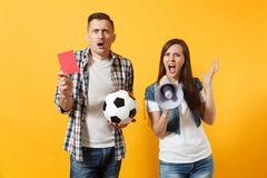 Angry fun expessive crazy couple, woman man football fans screaming, cheer up support team with soccer ball, megaphone. Red card isolated on yellow background stock photography