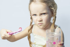 Angry and furioгs little girl not willing to brush her teeth. Over isolated background Royalty Free Stock Photos