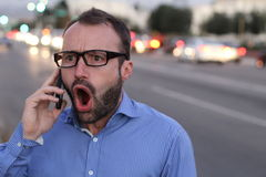 Angry furious businessman on cell phone call yelling and screaming in city.  Stock Photo