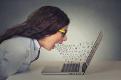 Angry furious businesswoman working on computer, screaming. With alphabet letter coming out of open mouth. Negative human emotions, facial expressions, feelings Stock Photo