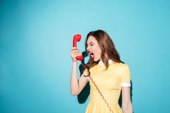 Angry furious girl in dress screaming at retro telephone tube. Portrait of an angry furious girl in dress screaming at retro telephone tube isolated over blue Royalty Free Stock Photos