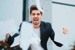 Angry furious male office worker throwing crumpled paper, having nervous breakdown at work, screaming in anger, stress royalty free stock photo