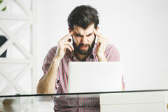 Angry furious male using laptop. In modern office. Irritation, stress and outbreak concept Stock Image