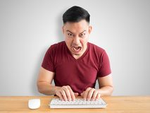 Angry and furious man works with computer. Royalty Free Stock Photos