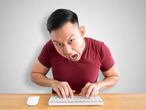 Angry and furious man works with computer. Angry and furious face of Asian man working with computer in the office Stock Images