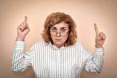 Angry and furious woman. Angry and furious middle aged woman wearing eyeglasses with index fingers up royalty free stock photo
