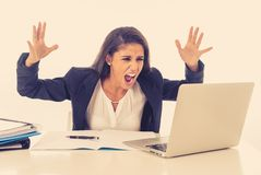 Angry furious stressed and overworked businesswoman yelling at her laptop in crisis lifestyle and long hours of work concept stock image