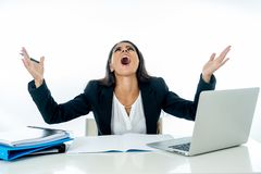 Young beautiful businesswoman shouting at her computer feeling mad and desperate stock images