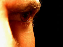 Angry Furrowed Brow. A man stares at himself angrily with a furrowed brow. The reflection can be seen in his eye stock photography