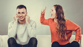 Angry fury woman screaming man closes his ears. Royalty Free Stock Images