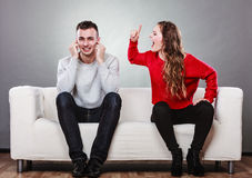 Angry fury woman screaming man closes his ears. Couple having argument - conflict, bad relationships. Angry fury women screaming men closing his ears Stock Photos