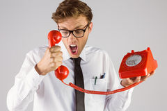 Angry geeky businessman holding telephone Stock Image