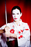 Angry Geisha. A portrait of young woman dressed as a Japanese Geisha warrior,  holding a Katana (Japanese Sword Royalty Free Stock Photos