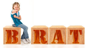 Angry Girl. Angry american 7 year old girl sitting on blocks spelling the word brat over white background Royalty Free Stock Photo