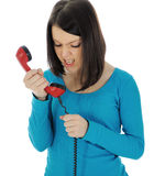Angry Girl. The angry girl with a red handset. Isolated on white background Royalty Free Stock Images