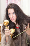 Angry girl in the fur coat with telephone Royalty Free Stock Photo