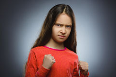 Angry girl with hand up yelling isolated on gray background. Stock Photo