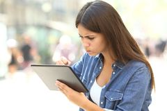 Angry girl having online problems with a tablet. In the street Royalty Free Stock Photos