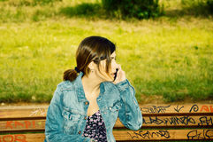Angry Girl holding cell phone. Angry Girl talking on cell phone, sitting on a chair on the nature in the park. Photo taken on: May 2014 Stock Image