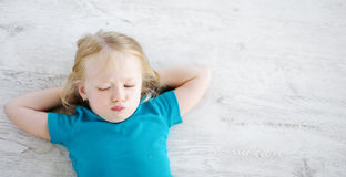 Angry girl lying on white wooden floor Royalty Free Stock Images