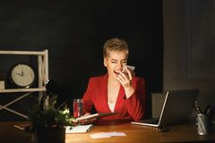 Angry girl at office shouting on mobile, staying late at working place. Young angry businesswoman arguing and shouting at someone on mobile. Girl staying late at Stock Photography