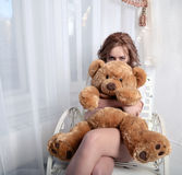 Angry girl with a plush bear sitting on a chair near the window Royalty Free Stock Image