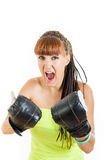 Angry girl in rage wearing boxing gloves ready to fight. And standing in combat position and trying to defend herself. Strength, power or competition concept royalty free stock photos