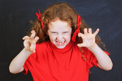 Angry girl in red t-shirt put out his tongue and  stand near bla Stock Images