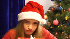 Angry girl in santa hat hides behind a christmas gifts stock video footage