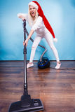 Angry girl in santa helper hat with vacuum cleaner Stock Image