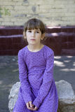 Angry girl seven years old. Wearing blue dress sitting on bench in the street royalty free stock photography